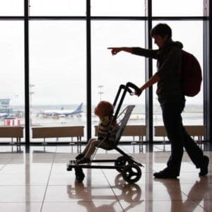 parent pushing baby in stroller in airport