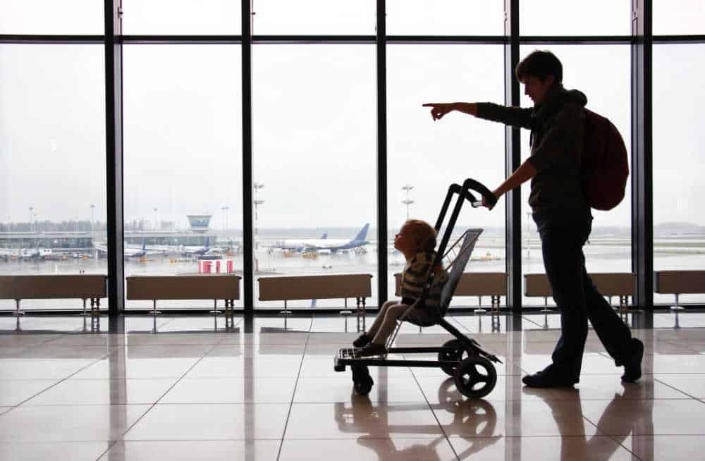 parent pushing baby in stroller at airport