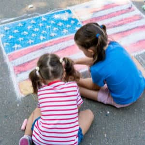 two young girls drawing american flag on driveway with chalk