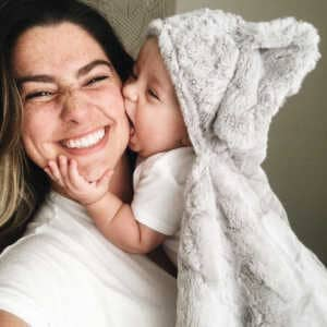 Mom smiling and holding baby while baby gives her a kiss
