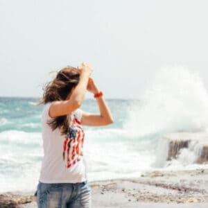 woman walking on beach wearing American flag shirt