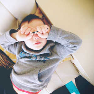 Boy covering his eyes with his hands.