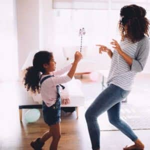 Mom and daughter playing game with blindfold and pinwheel