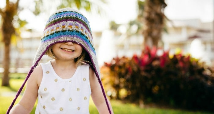 A little girl wearing a hat and smiling.
