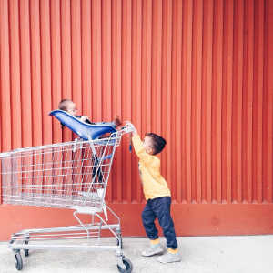 A boy pushing a grocery cart with a baby in it.