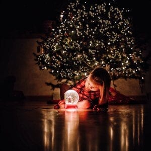 A child in a dark room under the christmas tree looking at a snow globe.