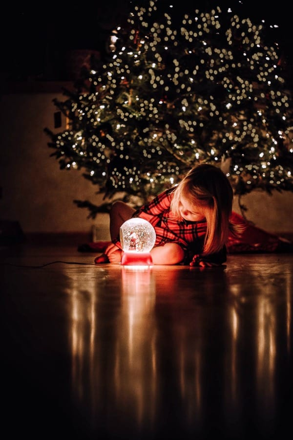 A child sitting in a dark room under the christmas tree looking at a snow globe.