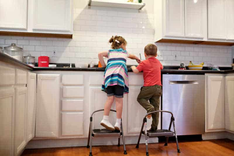 preschool-aged brother and sister standing at kitchen sink and doing dishes.