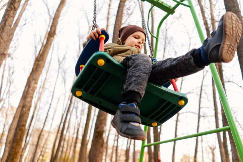 boy swinging in swing wearing fall weather clothes