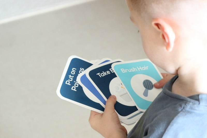 Child holding printable daily routine cards in hands.