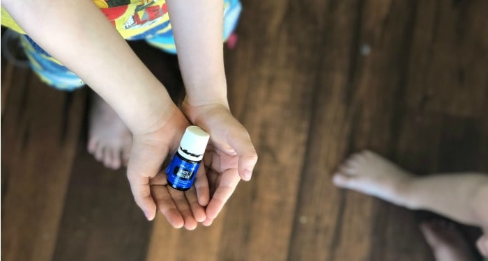 Little boy holding a bottle of white angelica essential oil cupped in his hands. He likes to use it with the help of his mother as an essential oil for stress.