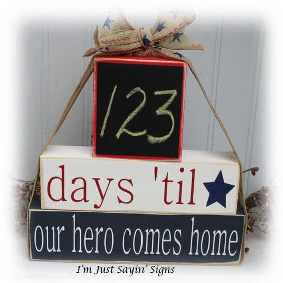 "A close up of a sign that says ""123 days \'till our hero comes home.\"""