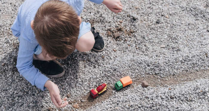 Overhead shot of 4 year old playing with matchbox trucks in the sand outside