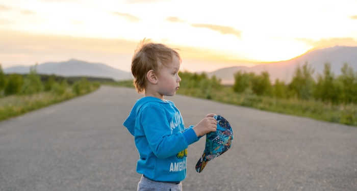 4 year old standing in country road watching sunset and holding baseball cap
