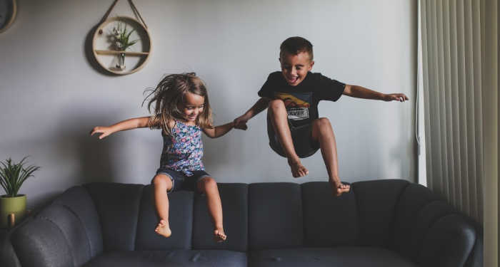 Two strong willed kids jumping on couch and laughing