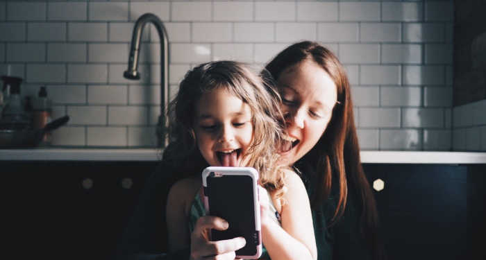 Mom and strong willed kid holding iphone and taking a selfie