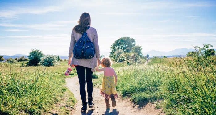 mom walking with daughter on a nature trail.