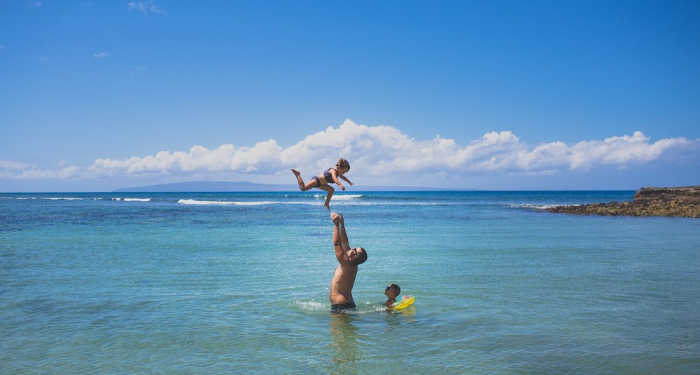dad throwing daughter in the air at pristine blue Caribbean beach vacation