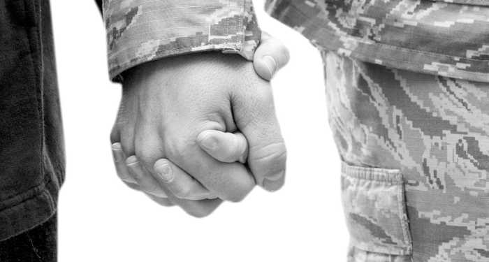Holding hands, sleeves of military man in uniform.