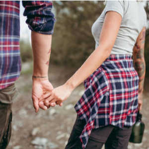 Man and woman in flannel shirts, holding hands.