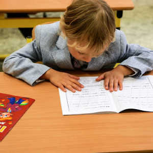 A child sitting at a desk doing school work.