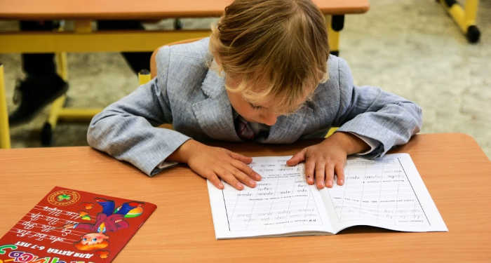 child focusing in the classroom reading a booklet at his desk