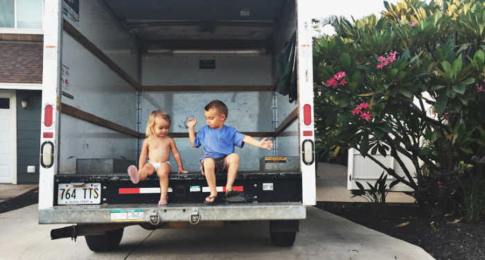 two young kids sitting in a empty moving truck