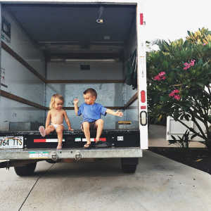 Two small children sitting in an empty moving truck.
