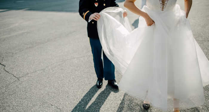 Military bride and groom walking in parking lot with groom holding the train.