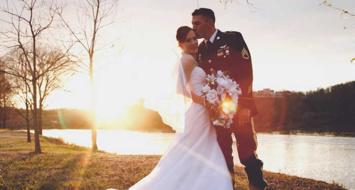 Military groom with his bride in white wedding dress posing near a lake.