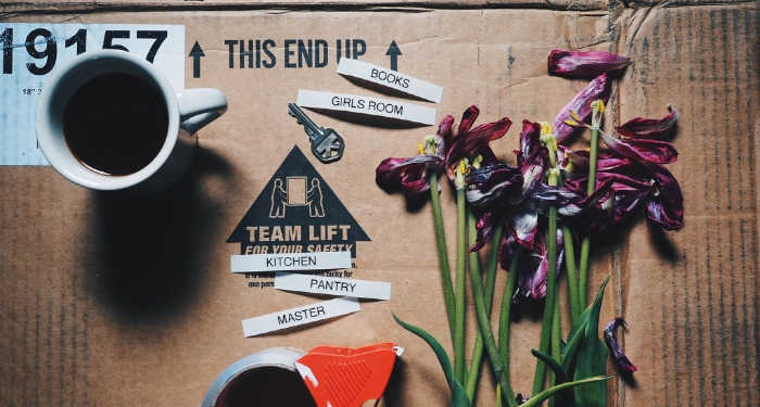 Moving labels, tape, small hand-picked flowers and a coffee mug over a flat cardboard box