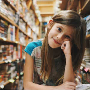 A girl sitting in a library looking at the camera.