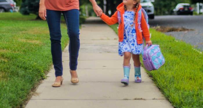 mom and daughter walking on sidewalk