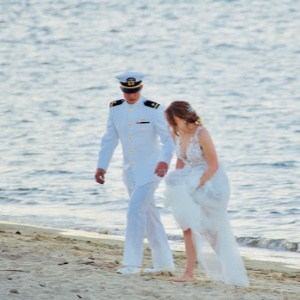 A military man in uniform walking on the beach with woman in wedding dress.