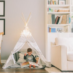 A young boy inside a play teepee reading books.