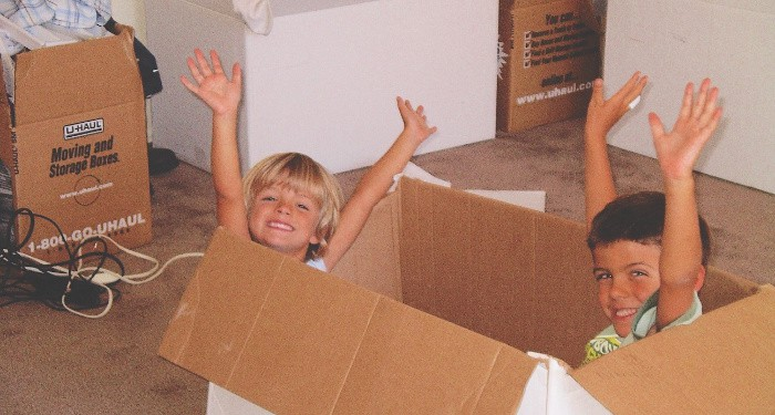 military kid in moving boxes