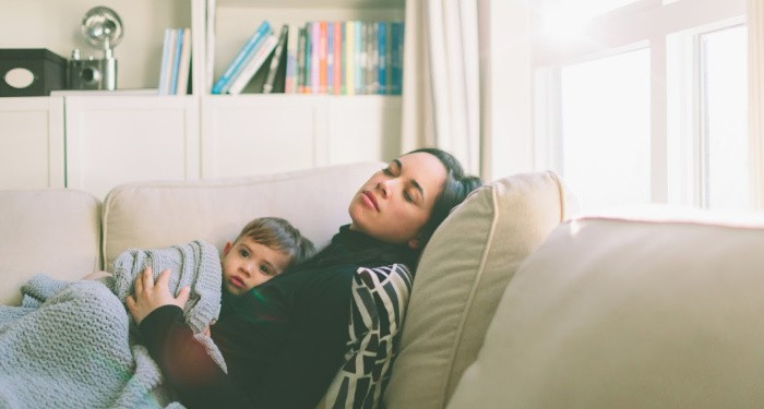 A mother sleeping on the couch with a toddler snuggled on her chest.