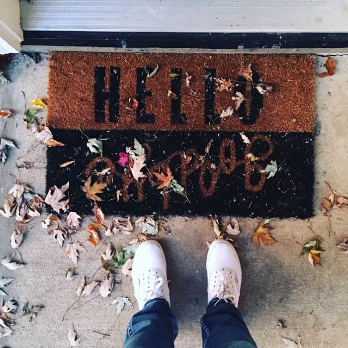Person standing at doormat that says Hello and Goodbye