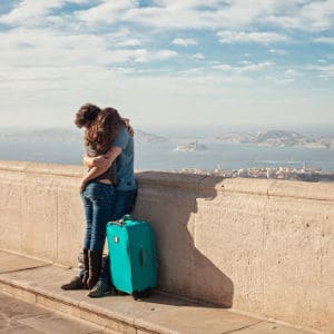 A person hugging goodbye, holding luggage