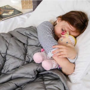 A toddler girl lying on a bed holding a stuffed doll.