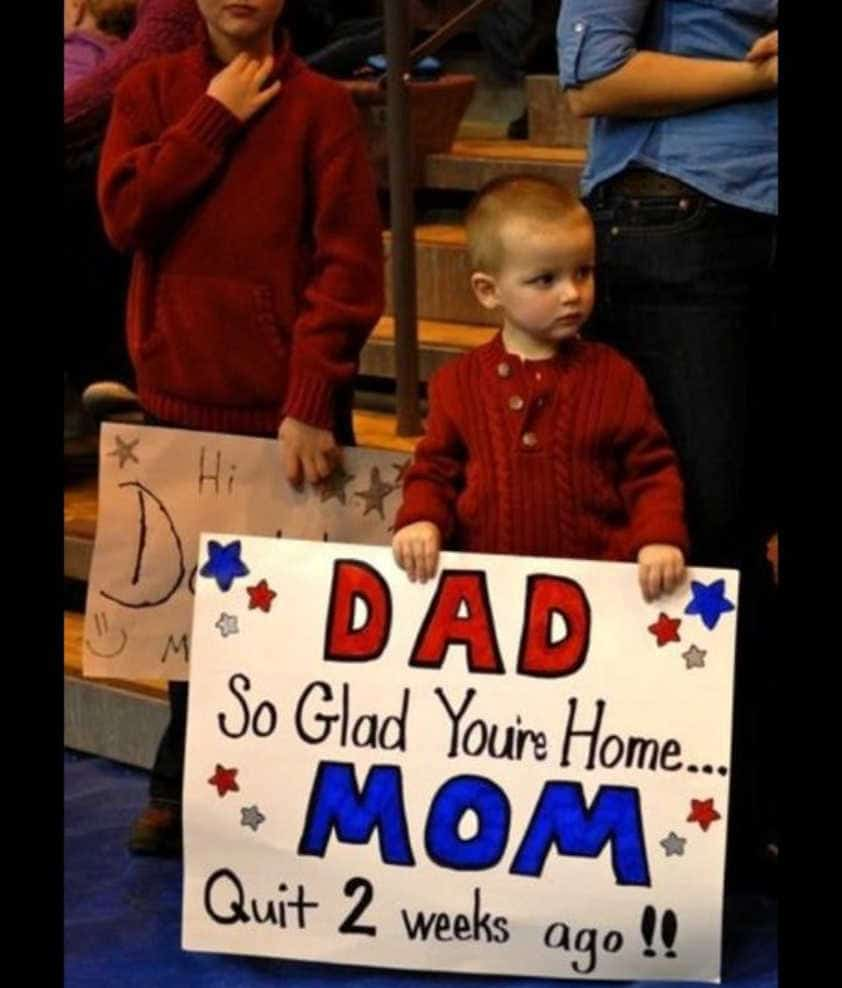 military kid holding homecoming sign