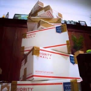 Stack of care packages in priority mail boxes