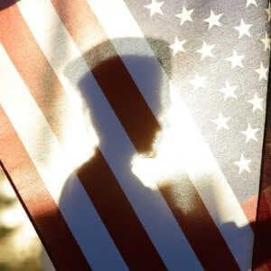 service member silhouette behind american flag