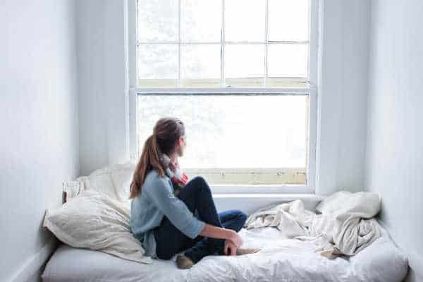 worried military girlfriend looking out window waiting for boyfriend to return home.