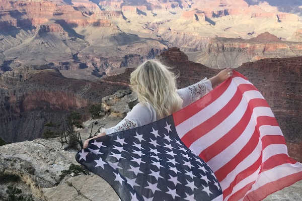 Military spouse with American flag overlooking grand canyon