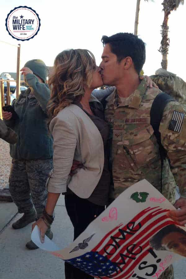 Military spouse kissing service member.