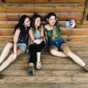 A group of young adult women sitting on a wooden bench
