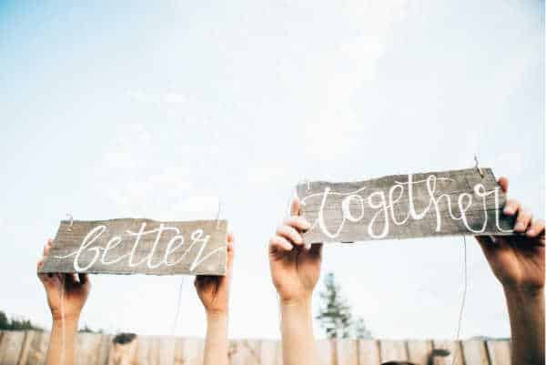 "couple arms and hands holding up sign that reads ""better together"""