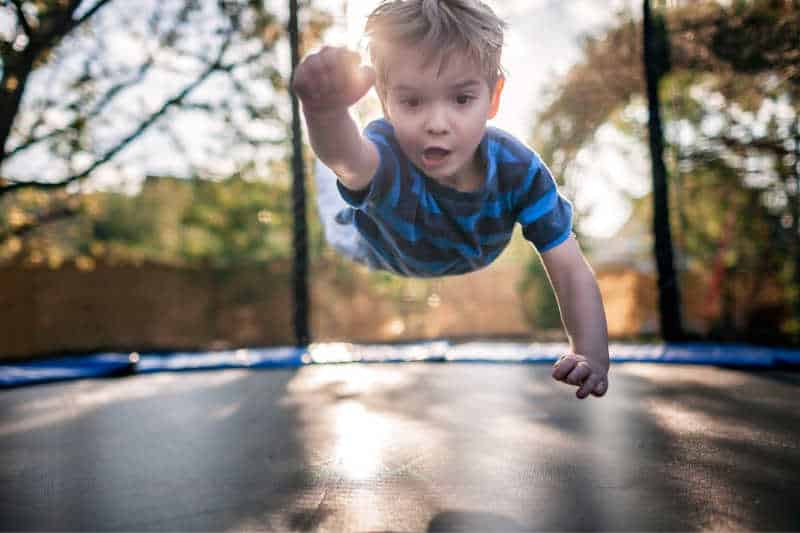 Child jumping on trampoline.