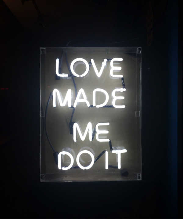 "Light up sign that reads ""Love made me do it."""